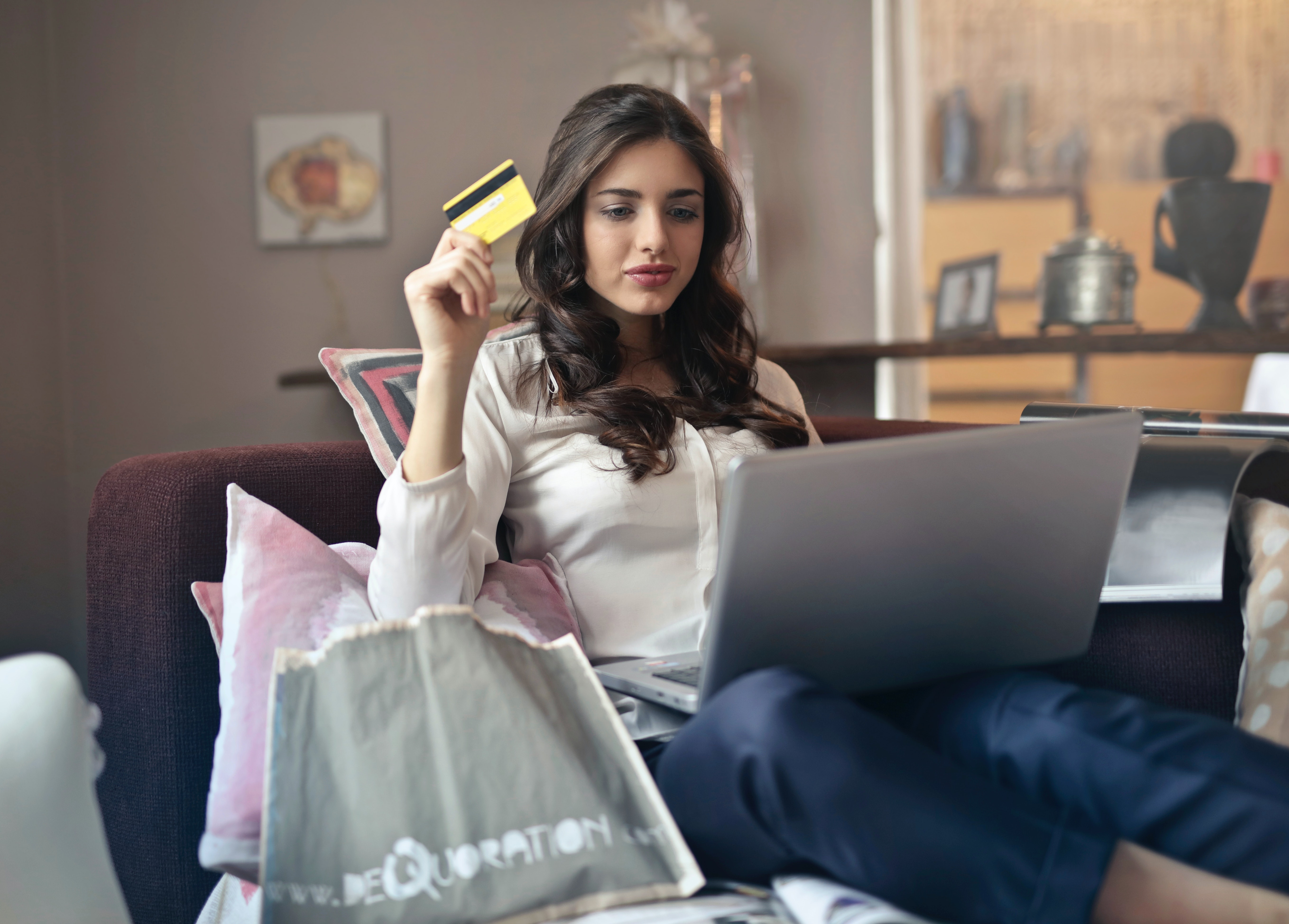 woman-shopping-online-with-card-holding-silver-laptop